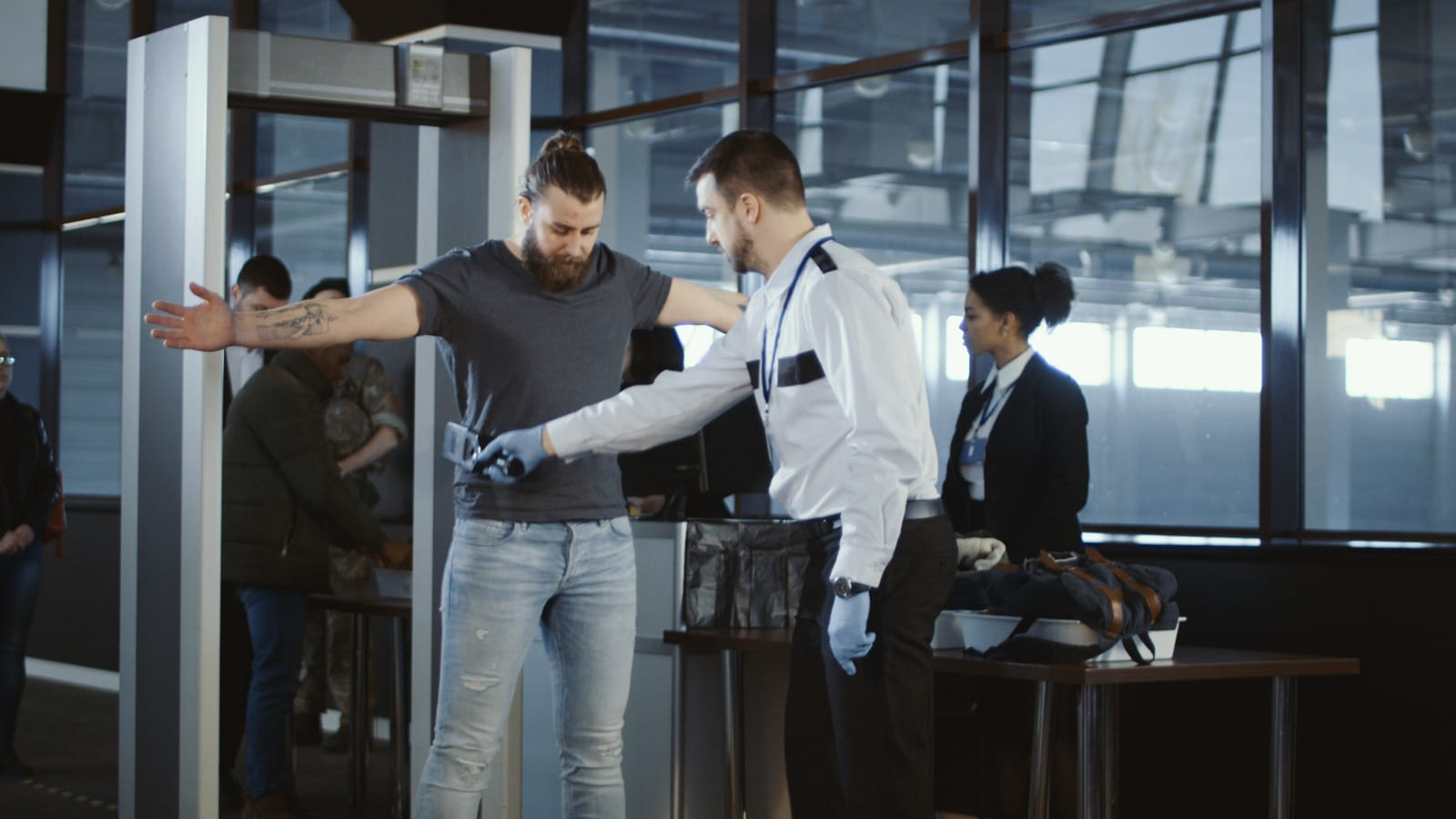 Man being screened with a metal detector at an airport.