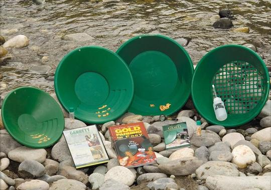 Garrett Deluxe Gold Panning Kit display on a rocky river bank.
