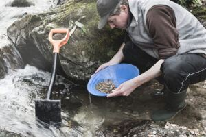 Man panning for gold in a stream.