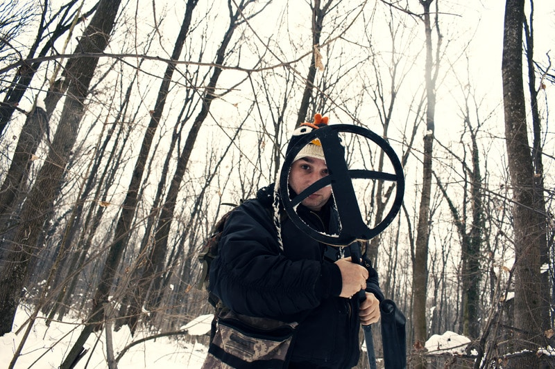 Person holding a large size search coil in the woods.