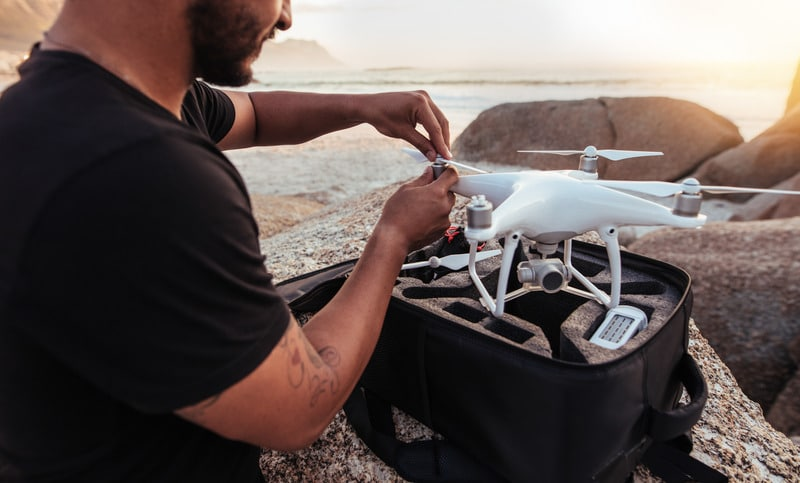 Young man sitting at rocky beach with a drone. Man setting up / dismantling a drone.