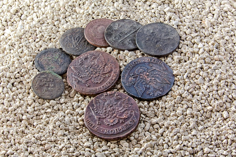 Old copper coins in the sand.
