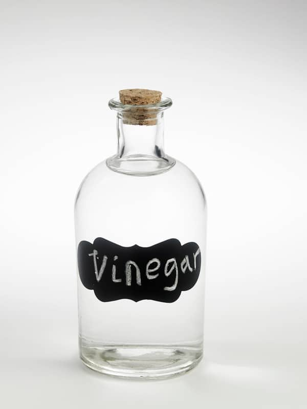 Jar of white vinegar with cork top.