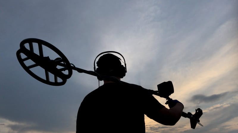 Silhouette of a man holding a metal detector