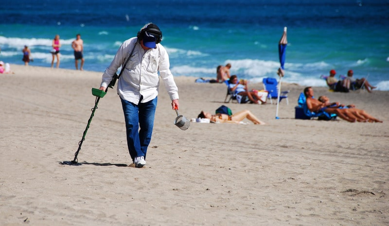 Man searching the beach with a metal detector and sand scoop.