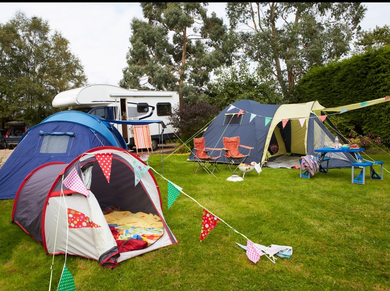 Campsite With Pitched Tents And Campervan