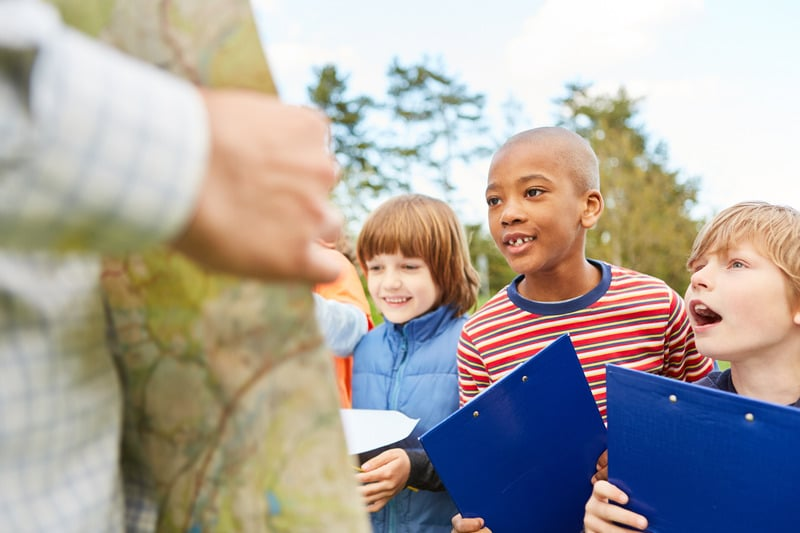 Children as detectives and explorers on a treasure hunt or scavenger hunt with clipboard