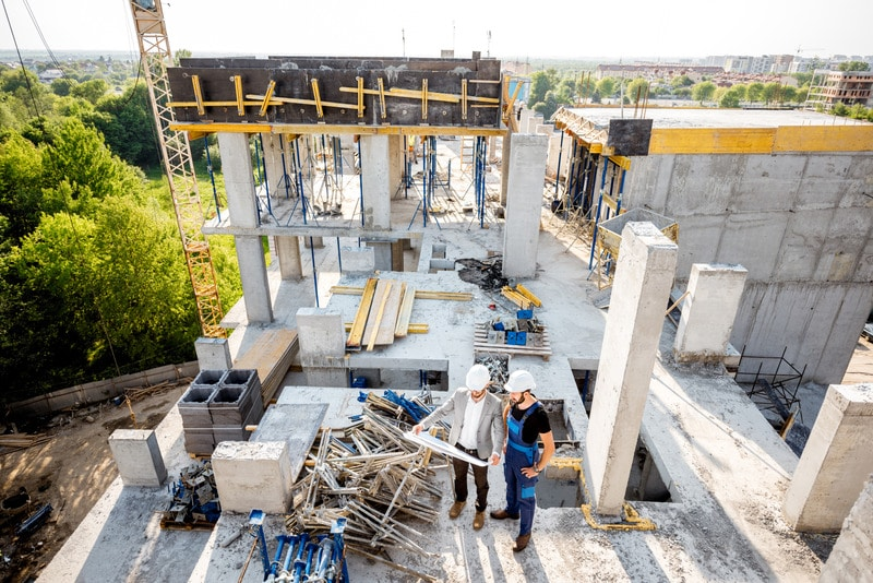Top view on the construction site of residential buildings during the construction process with two workers standing with drawings