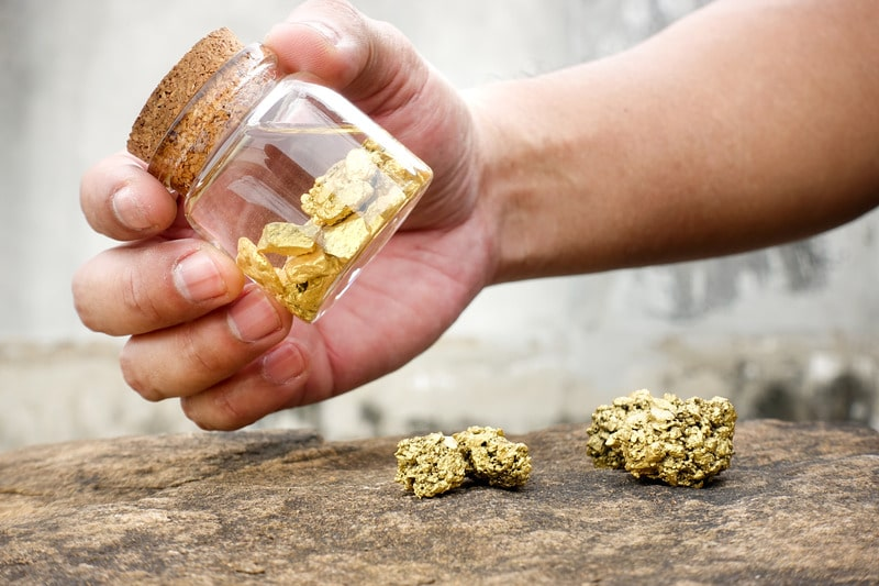 Human hands are swinging bottles that contain pure gold minerals found in mines.