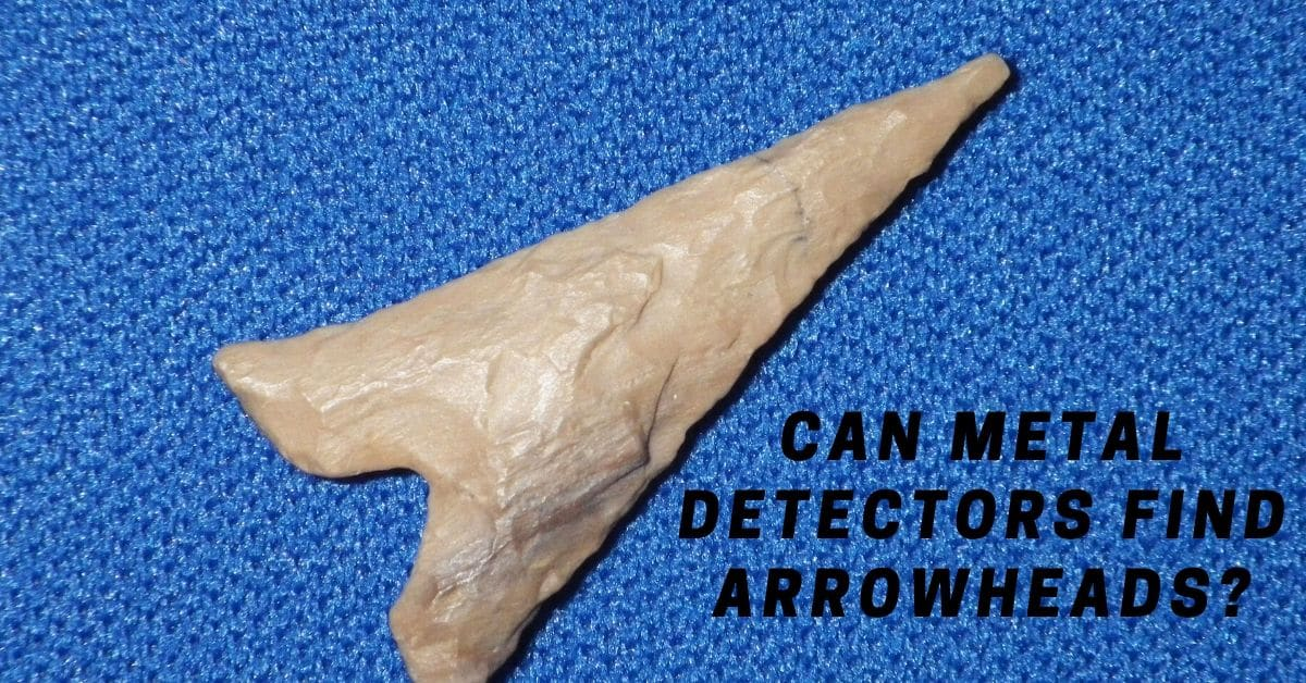 Arrowhead on a blue fabric background and the words Can metal detectors find arrowheads?