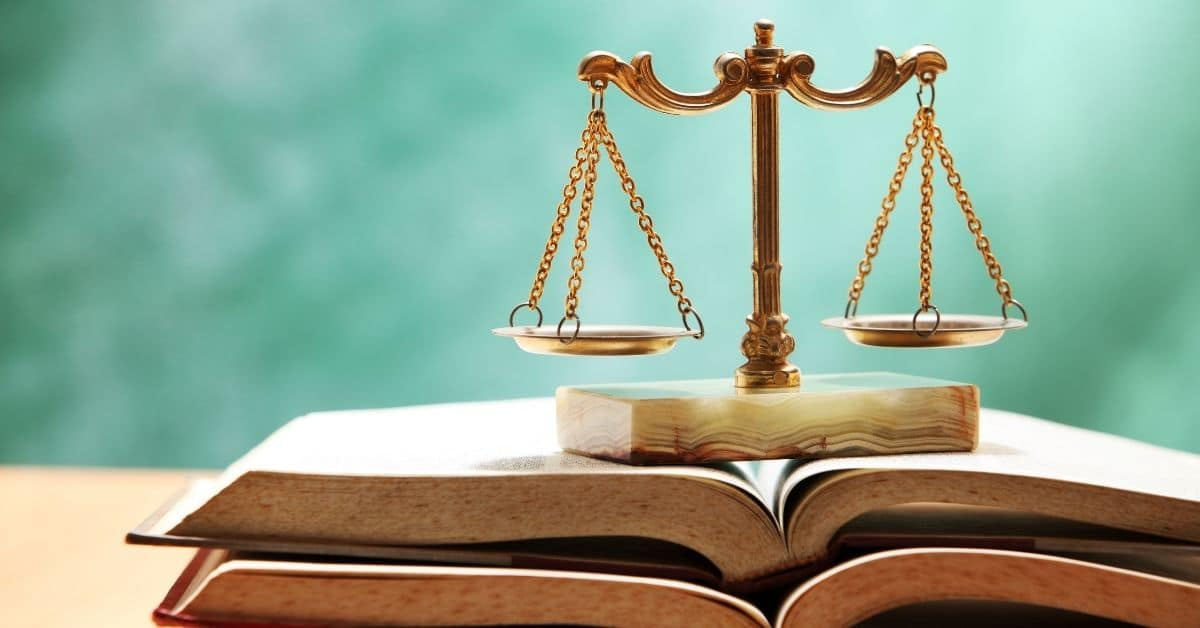 The scale of justice on top of open books.