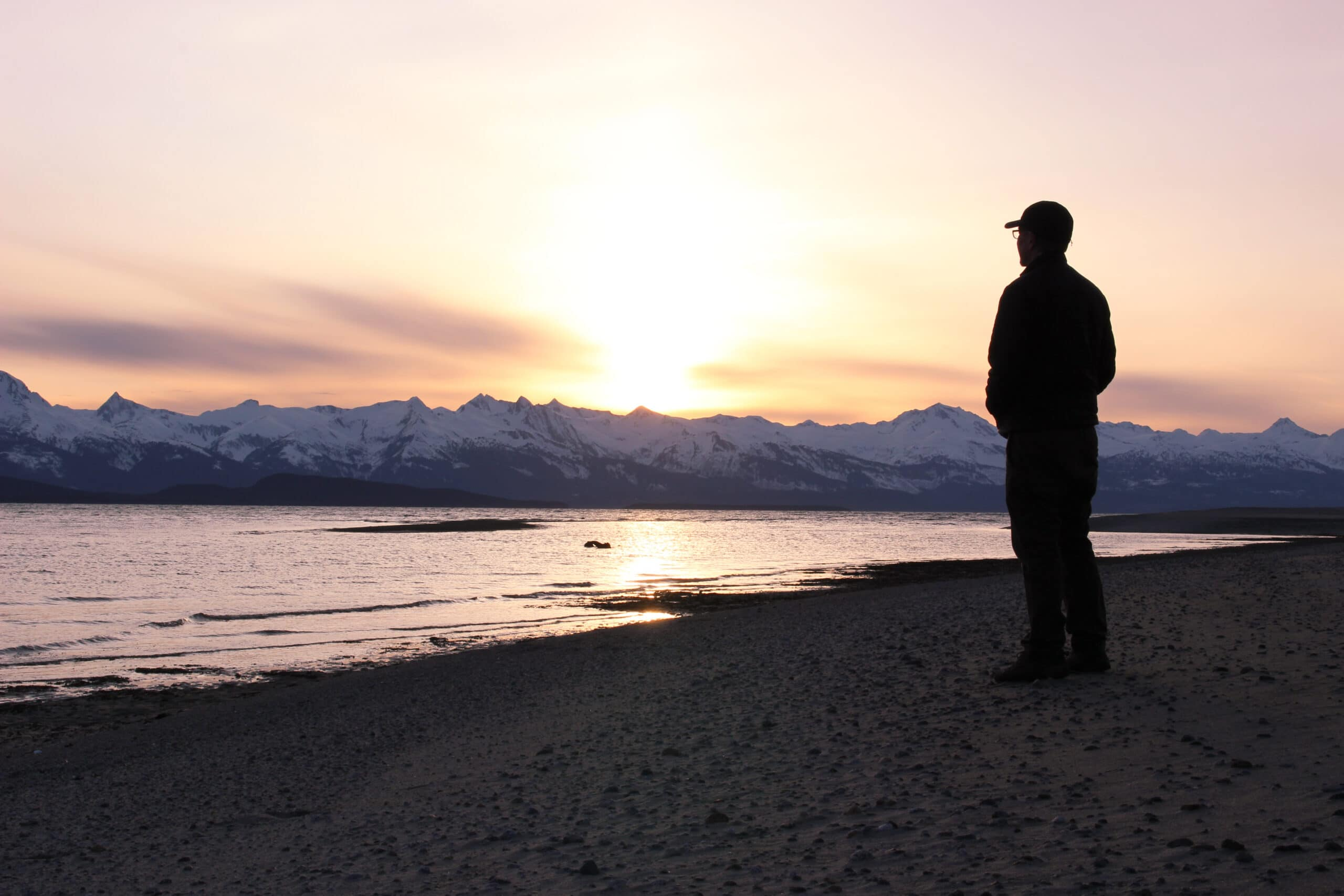 Silhouette of Man on Eagle Beach on Lynn Canal Overlooking the Chilkat Mountain Range in Southeast Alaska