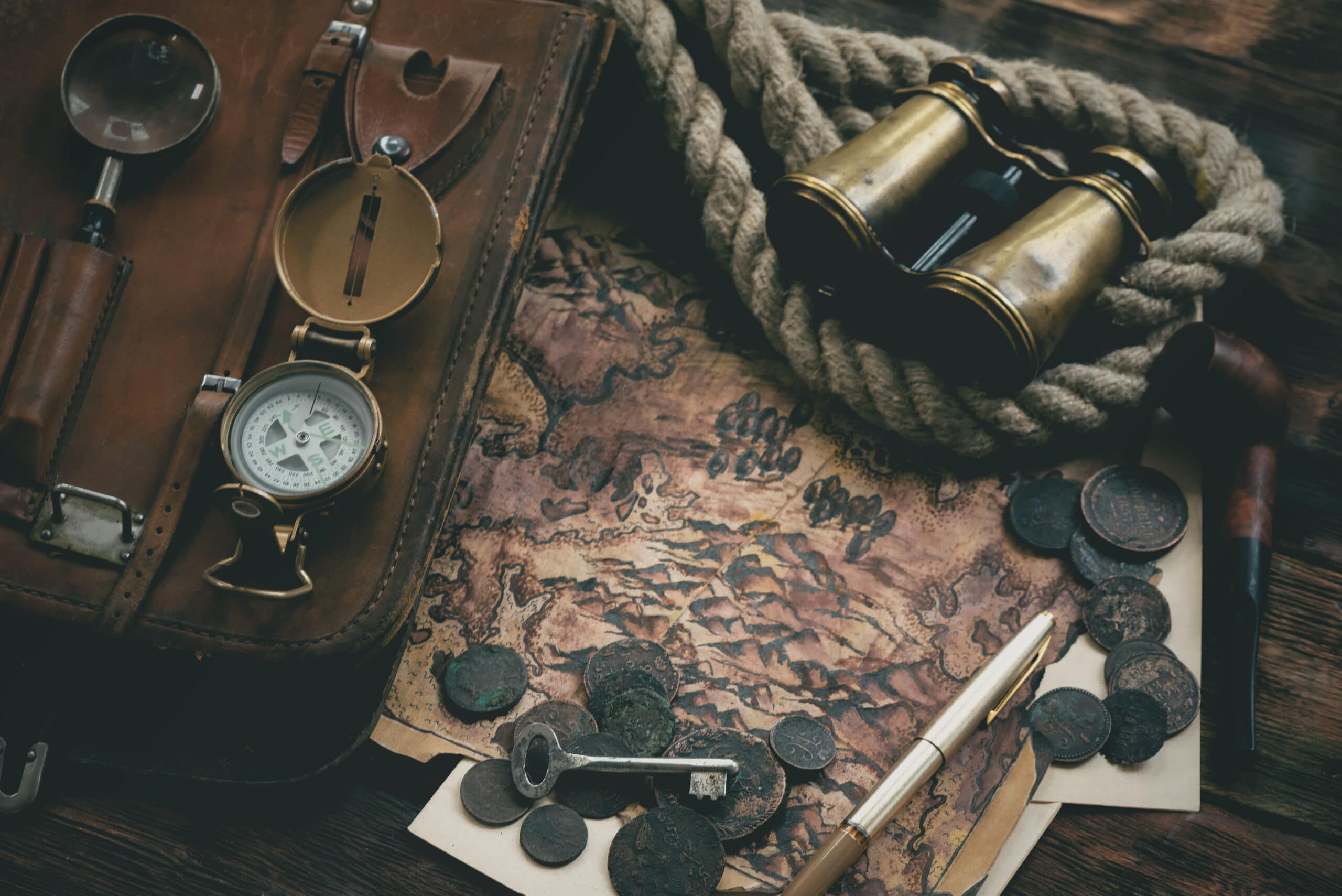 Treasure map and adventurer accessories on a wooden table background. Treasure hunt concept background.