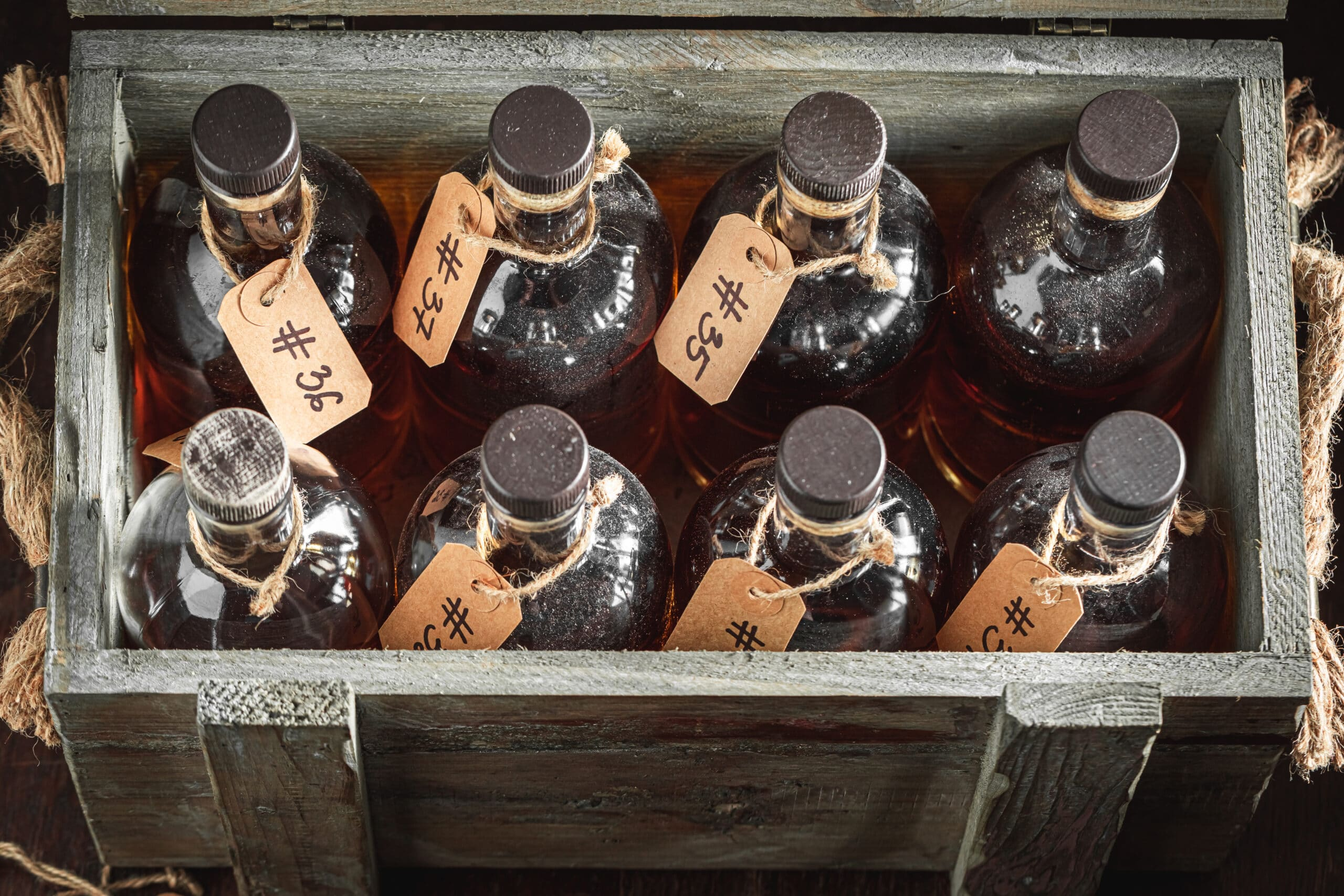 Hand crafted whisky on wooden box with bottles from distillery