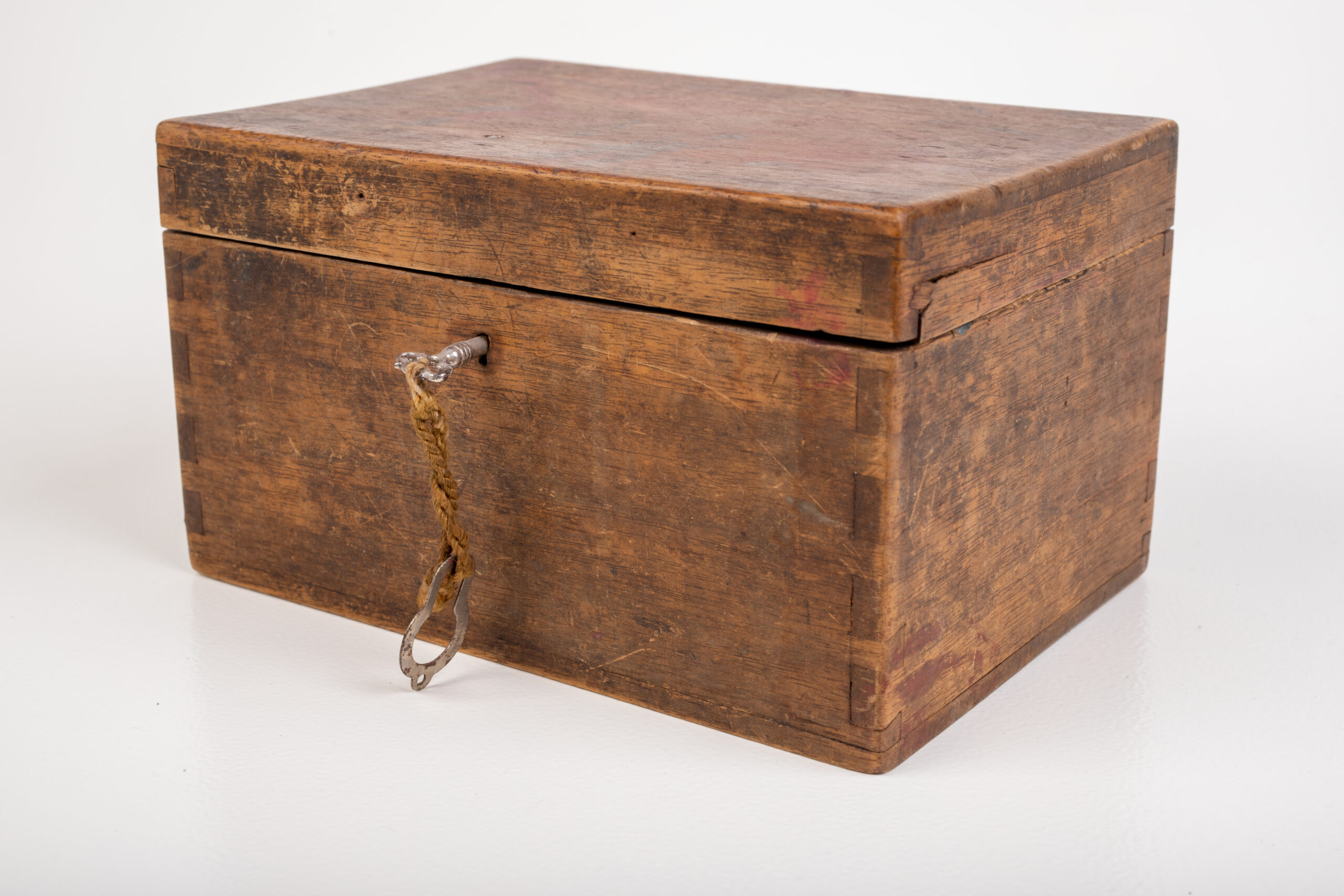Old wooden case and small key. A mysterious wooden container. Light background.